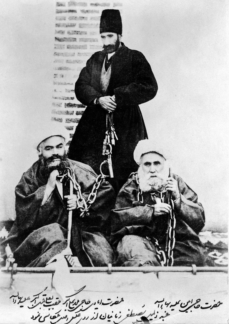Hands of the Cause Hají Ákhúnd and Hájí Amín (seated), in chains and stocks with