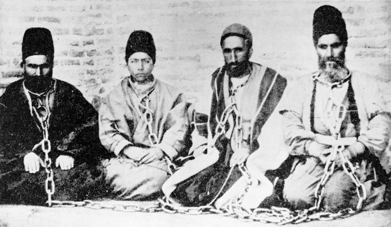 A Bahá'í father and son (at left) in chains after being arrested with fellow