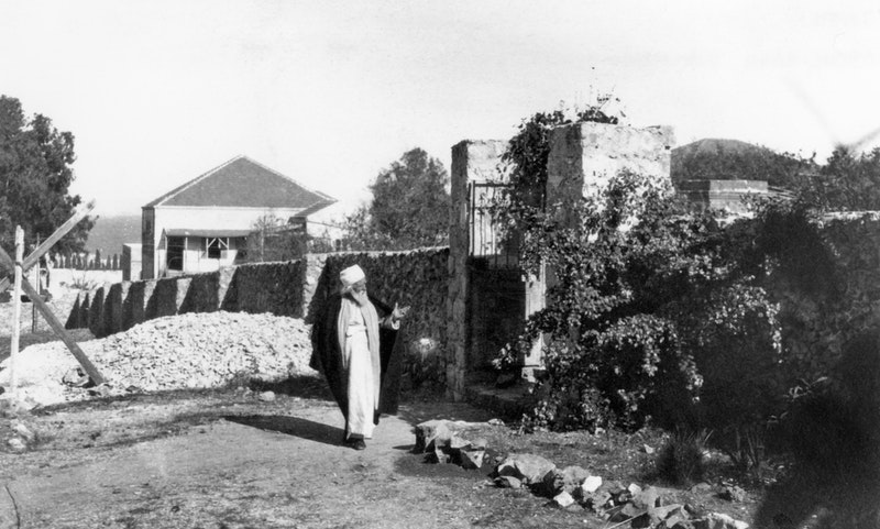 'Abdu'l-Bahá walking outside 7 Haparsim Street in Haifa, c. 1919