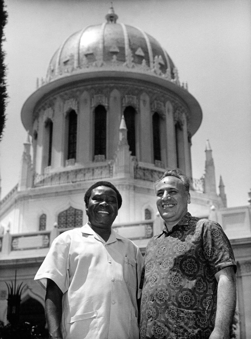 Hands of the Cause Enoch Olinga (left) and Rahmatu'lláh Muhájir (right) in front of the Shrine of the Báb, 1973